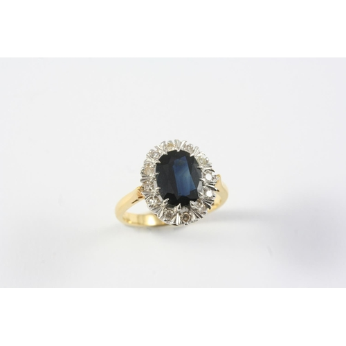 1340 - A SAPPHIRE AND DIAMOND CLUSTER RING the oval-shaped sapphire is set within a surround of circular-cu...