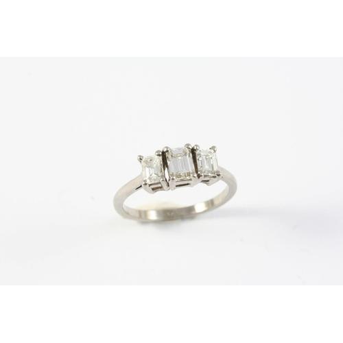 1341 - A DIAMOND THREE STONE RING the three graduated emerald-cut diamonds are set in platinum. Size M 1/2...