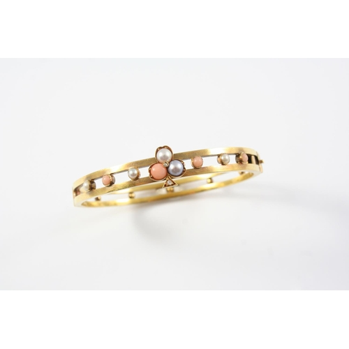 1364 - A GOLD, CORAL, PEARL AND DIAMOND HALF HINGED BANGLE the openwork design is centred with a clover lea...