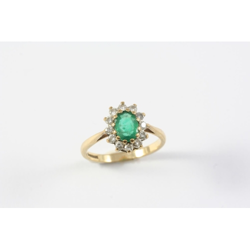 1383 - AN EMERALD AND DIAMOND CLUSTER RING the oval-shaped emerald is set within a surround circular-cut di...
