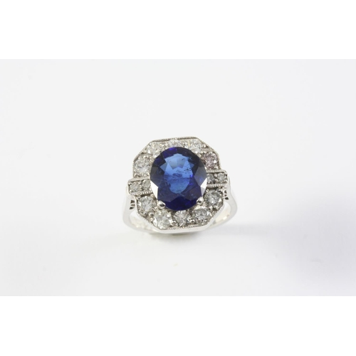 1420 - A SAPPHIRE AND DIAMOND CLUSTER RING the oval-shaped sapphire is set within a surround of circular-cu...