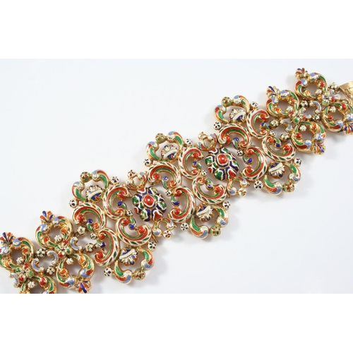 1438 - A GOLD AND ENAMEL PANEL BRACELET the openwork scroll design set overall with polychrome enamel decor...