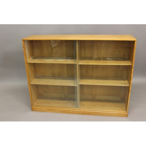 1510 - COTSWOLD SCHOOL BOOKCASE a well made oak bookcase with four adjustable shelves, glazed doors and pan...