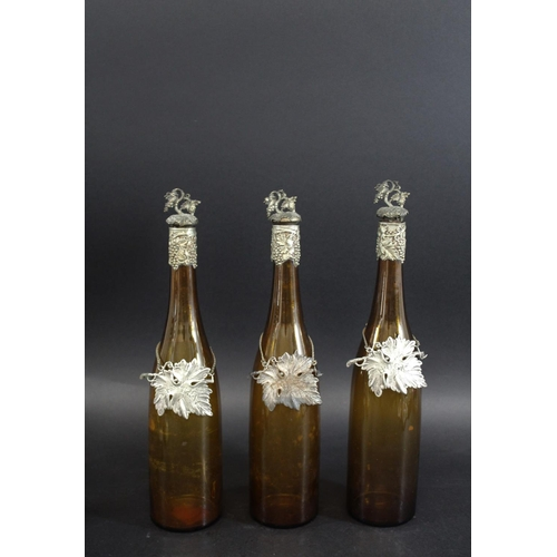 1612 - VICTORIAN GLASS DECANTERS & WINE LABELS a set of three amber coloured glass decanters, with metal mo...