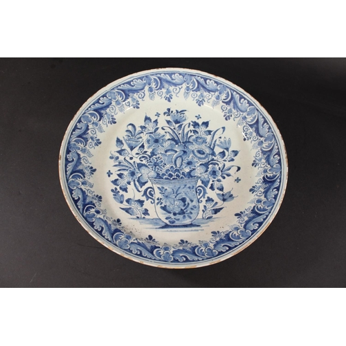 1661 - 18THC DUTCH DELFT DISH a large delft blue and white dish, painted in the centre with a vase and a va...