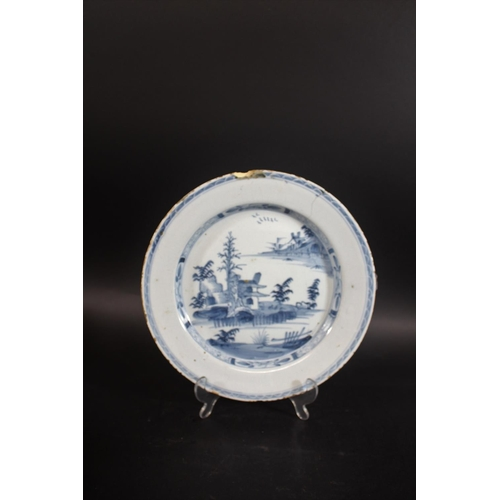 1671 - 18THC DELFT DISH a blue and white dish painted with buildings within an oriental style landscape, da...