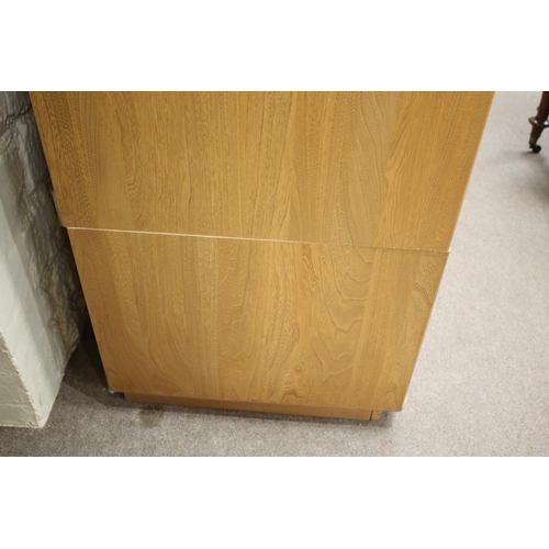 1504 - ERCOL WARDROBE a large light elm wardrobe, the top section with two doors to reveal a shelf and hang...
