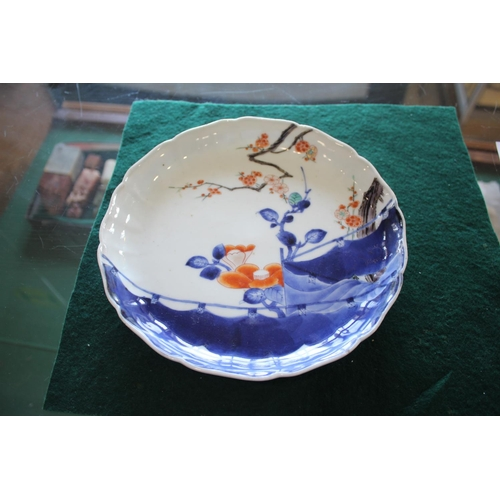 1744 - JAPANESE KAKIEMON DISH a lobbed dish painted with tree blossom in blue, red and white colours. Bears...