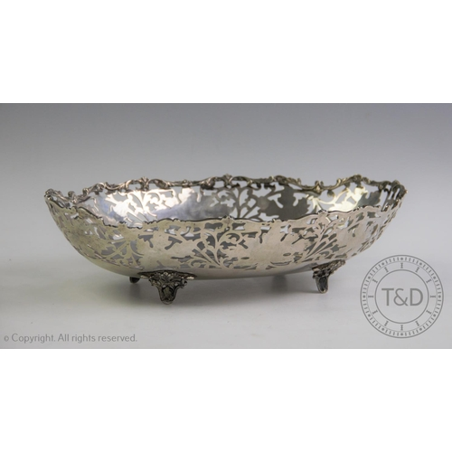 44 - A continental silver bowl, of pierced oval form with acanthus cast rim raised on four cast out-swept...
