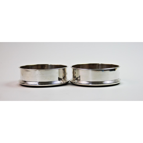 2 - A pair of silver mounted bottle coasters, P H Vogel & Co, Birmingham 1998, of circular plain polishe...