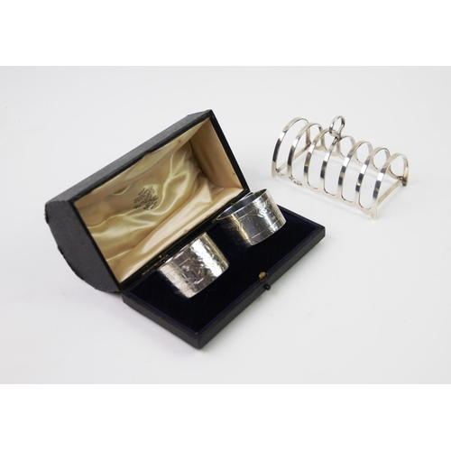 25 - A George V silver toast rack, Barker Brothers Silver Ltd, Birmingham 1929, of six division, plain po...
