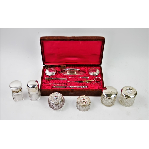 27 - An Edwardian harlequin silver backed manicure set, comprising: two silver topped glass jars, brush, ...