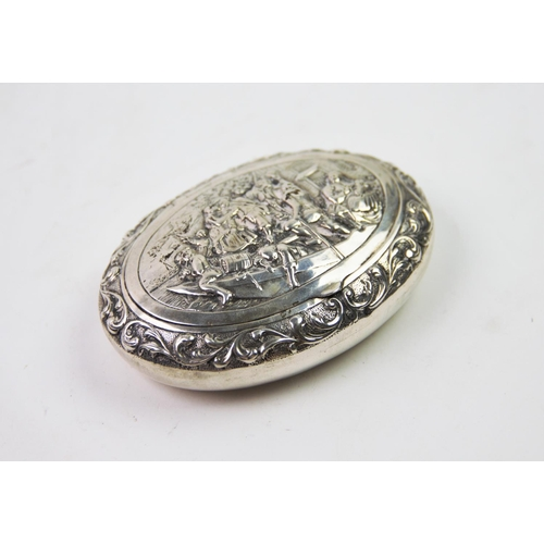 37 - A 19th century Dutch silver snuff box, of oval form, the cover decorated with embossed figures on a ...
