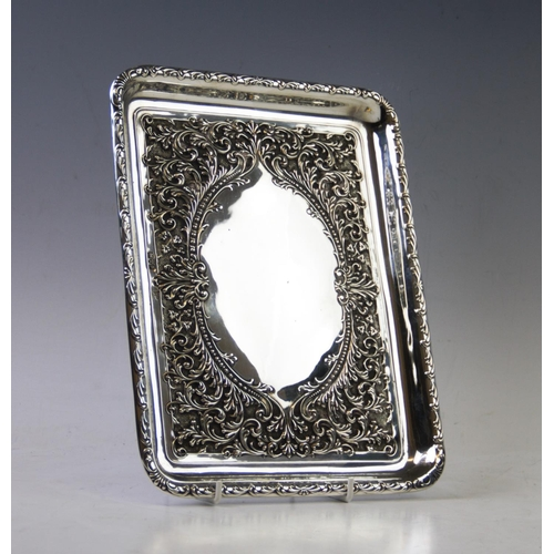 7 - An Edwardian silver tray, Walker & Hall, Chester 1906, of rectangular form, the central vacant carto...