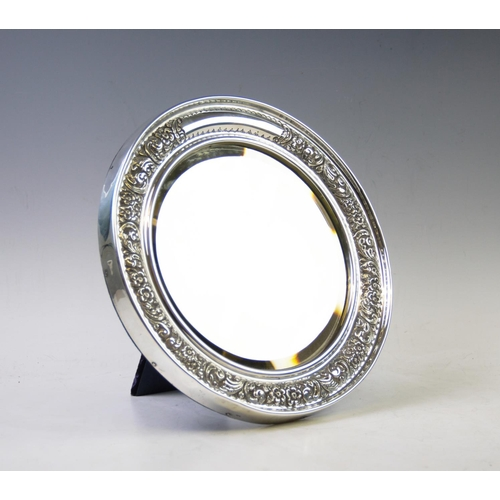 8 - A Victorian silver mirror, probably William Davenport, Birmingham 1900, of circular form, with embos...