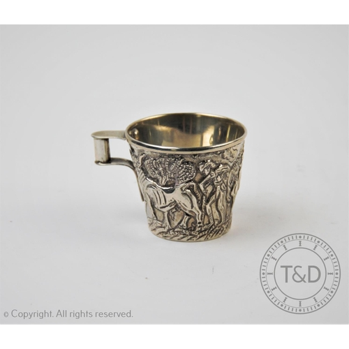 26 - A continental white metal replica of the 'Vaphio' cup, of tapering form, with relief depicting bull ...