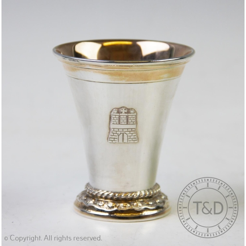 8 - A German white metal cup, of plain polished tapering form, rope twist detail to the stepped base, wi...