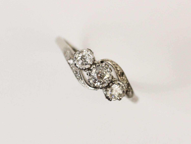 A diamond three-stone ring, comprising a...