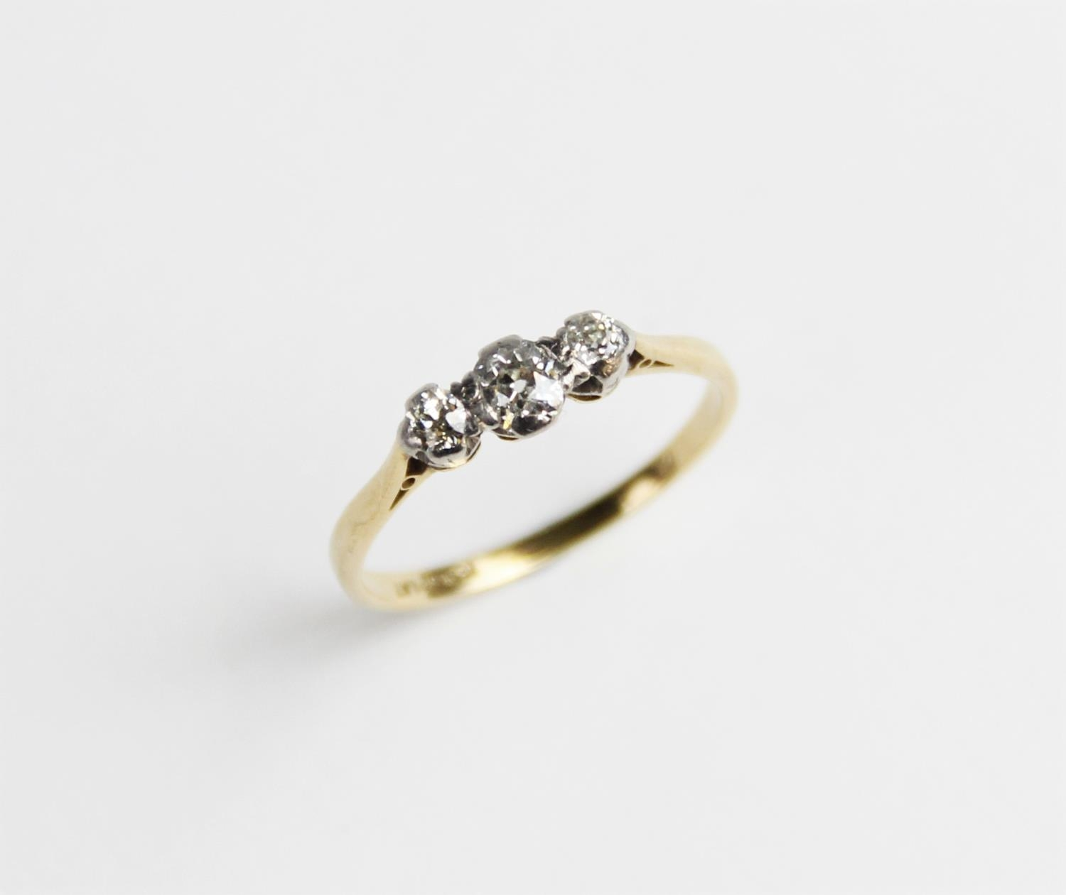 A diamond three stone ring, the central ...