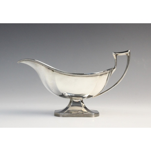 12 - A George V silver sauce boat by Harrison Brothers & Howson, London 1911, of faceted form on raised o...