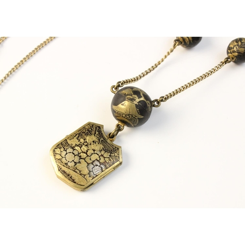 39 - A Chinese yellow metal and niello locket pendant, of shield form decorated with pagodas, flowers and...