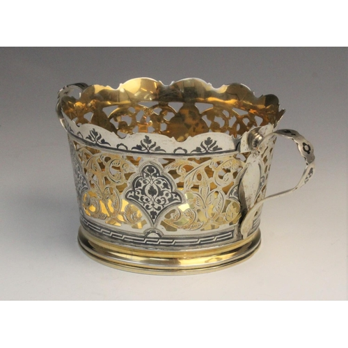 50 - A Russian silver gilt and niello twin-handled wine coaster, of tapering form with pierced foliate de...