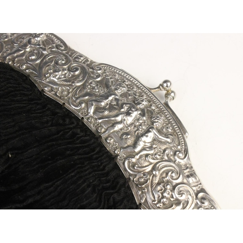 54 - An early 20th century continental silver mounted evening purse, the silver mount embossed with putti...