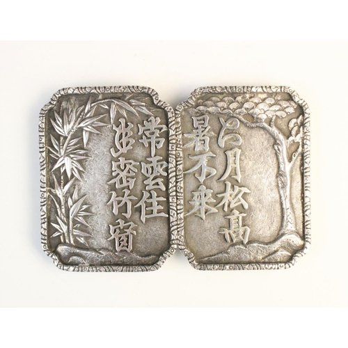 59 - A Chinese export silver belt buckle, comprising two rectangular panels with canted corners, embossed...