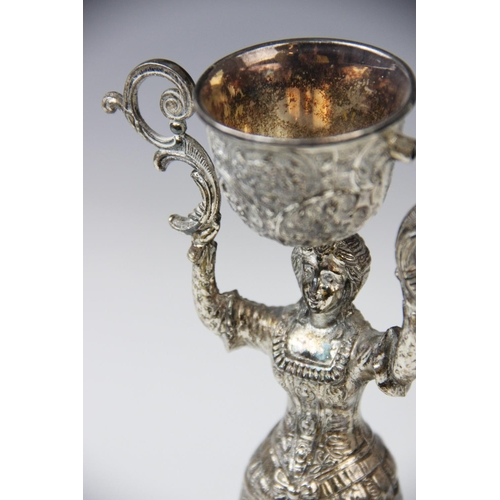 2 - A continental silver plated wager cup, in the form of a finely dressed lady with full skirt holding ...