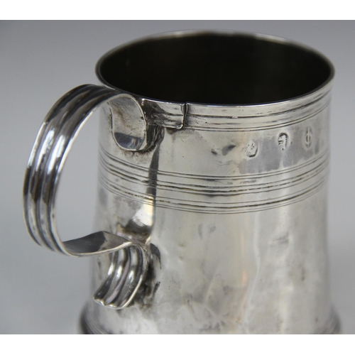 23 - A Queen Anne silver mug, of tapered cylindrical form on raised circular foot with simple loop handle...