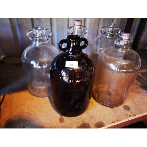 38 - Four clear glass demi-johns and brown tinted demi-john...