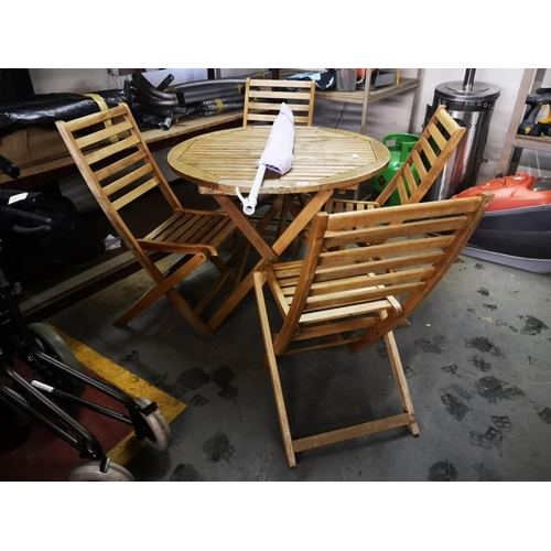49 - Round hardwood folding slatted garden table approx 3'dia plus four hardwood chairs and parasol in ex...