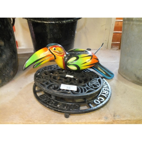 30 - Three cast iron trivets and garden toucan ornament...