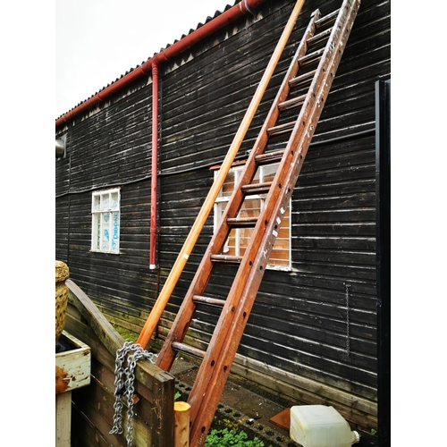 27 - Two stage 14' extending wooden ladder...