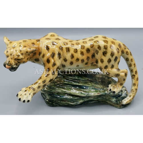 31 - ELITE POTTERY MODEL OF A CHEETAH ON A  ROCK...