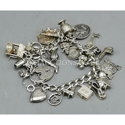 22 - PRESENTED AS A SOLID SILVER CHARM BRACELET With 29 CHARMS (Weight 84 Grams) (Hallmarked For Birmingh...