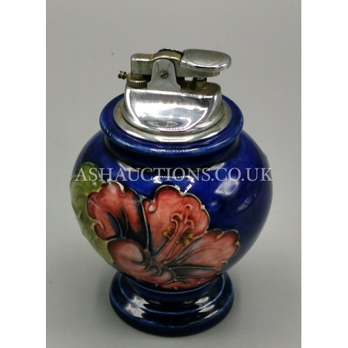 39 - MOORCROFT TABLE CIGARETTE LIGHTER IN THE HIBISCUS DESIGN ON BLUE GROUND...