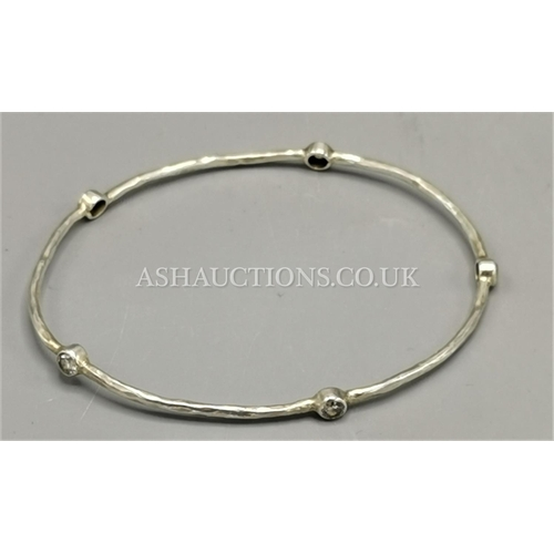 60A - PRESENTED AS A SILVER (925) STONE SET BANGLE...