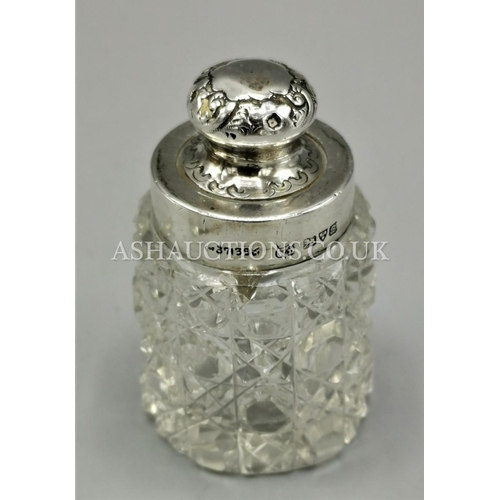 15 - PRESENTED AS A SILVER TOPPED CUT GLASS PERFUME BOTTLE WITH SILVER COVERED STOPPER...