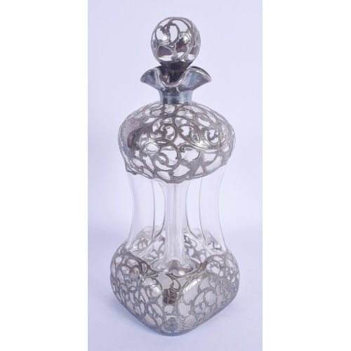1031 - AN ART NOUVEAU SILVER OVERLAID DECANTER AND STOPPER. 25 cm high....