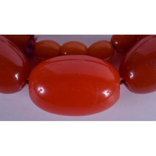 1045 - A LARGE ART DECO  AMBER CATALIN BAKELITE NECKLACE. 107 grams. 64 cm long, largest bead 3.75 cm wide....