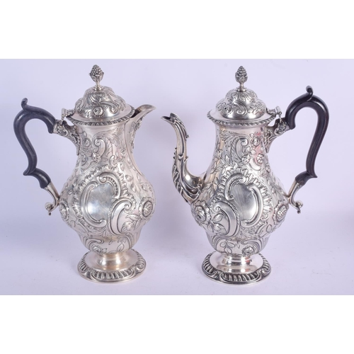 1118 - A MATCHED PAIR OF EDWARDIAN SILVER COFFEE POTS. London 1904 & 1905. 1770 grams. 29 cm high....