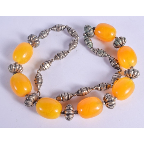 1203 - A SILVER AND AMBER NECKLACE. 101 grams. 60 cm long, largest bead 2.5 cm x 2 cm....