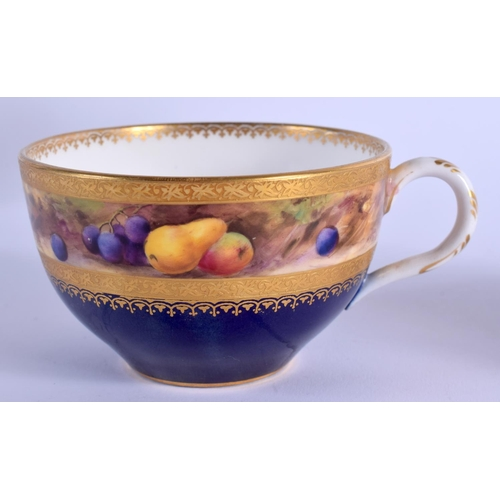 134 - A ROYAL WORCESTER TEACUP AND SAUCER painted with a band of fruit on a mossy bank above a blue and gi...
