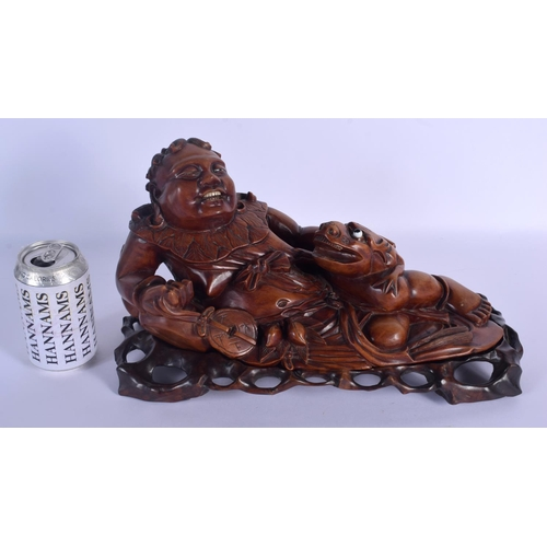 1558 - A LARGE 19TH CENTURY CHINESE CARVED HARDWOOD FIGURE OF A SCHOLAR Qing, modelled recumbent beside a b...