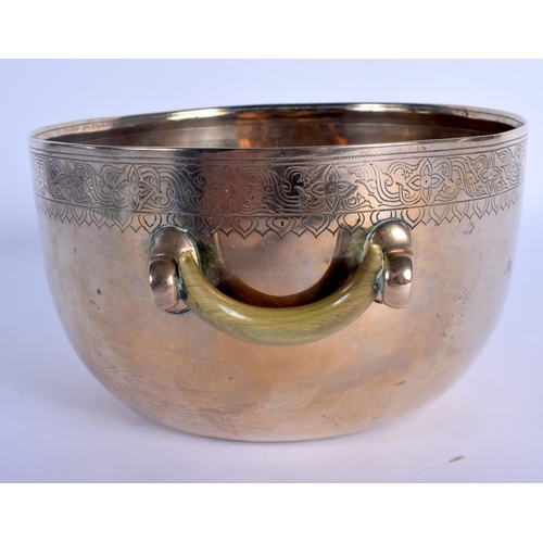 1562 - A 19TH CENTURY INDO TIBETAN TWIN HANDLED POLISHED BRASS CENSER with carved rhinoceros horn handles, ...