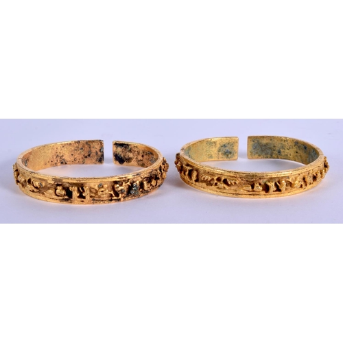 1682 - AN UNUSUAL PAIR OF 18TH/19TH CENTURY CHINESE GILT BRONZE BANGLES Qing, decorated with figures and la...