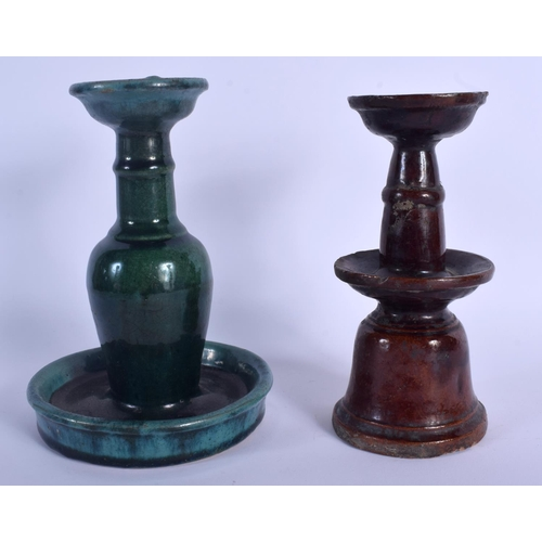 2004 - TWO 19TH CENTURY CHINESE POTTERY BUDDHISTIC POTTERY CANDLESTICKS. Largest 20 cm high. (2)...