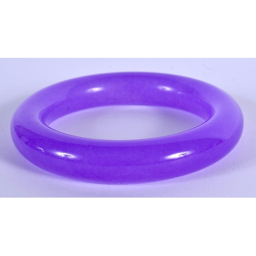 2105 - A CHINESE CARVED PURPLE JADE BANGLE 20th Century. 8 cm diameter....