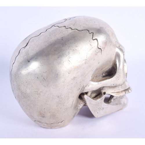 770 - A CONTEMPORARY SILVER PLATED SKULL. 11 cm x 9 cm....